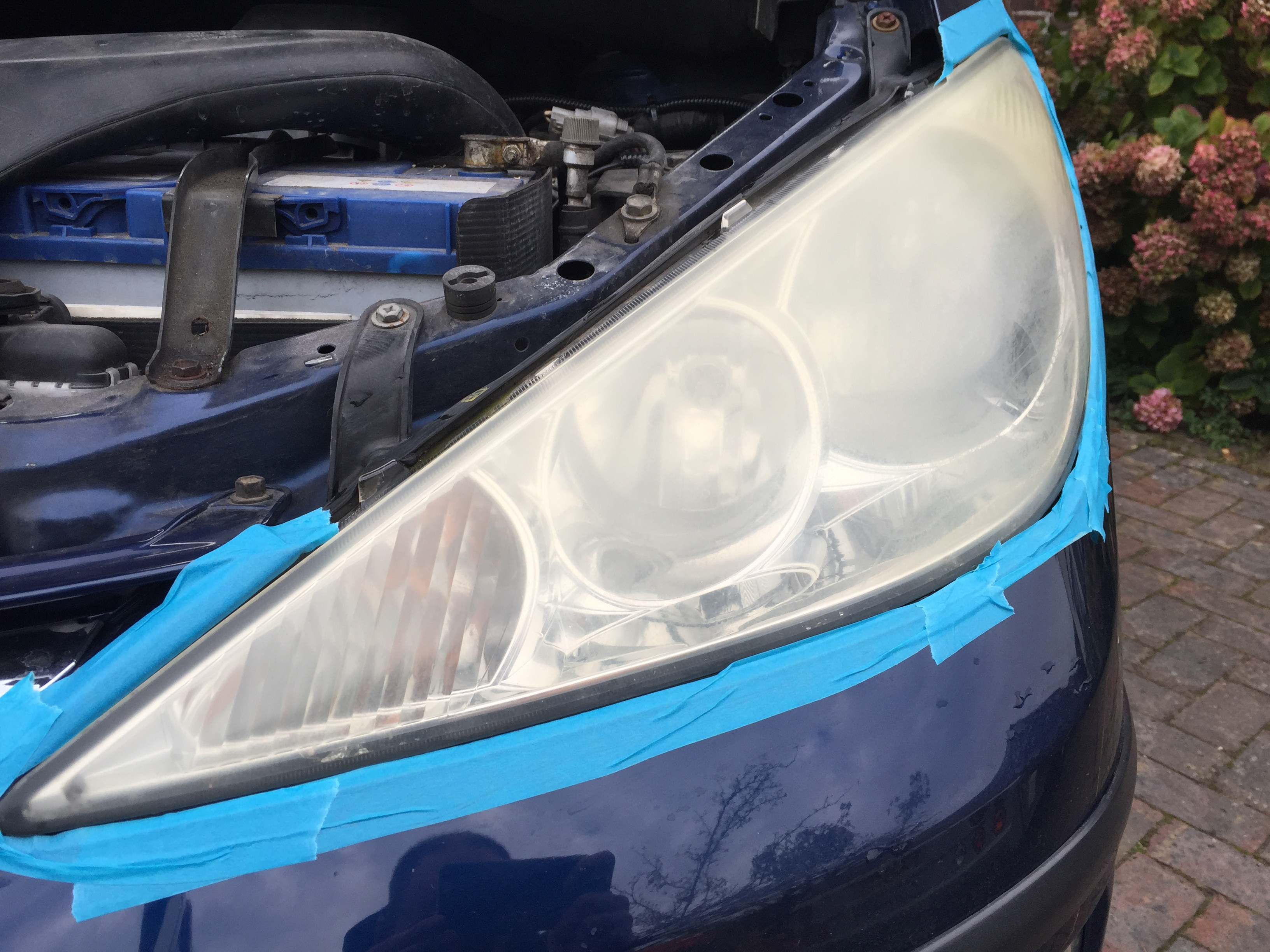 Yellow corroded plastic cloudy headlight before cleaning and polishing in Sussex Brighton